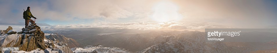 Mountaineer sunrise snow summit golden dawn panorama Lake District UK : Stock Photo