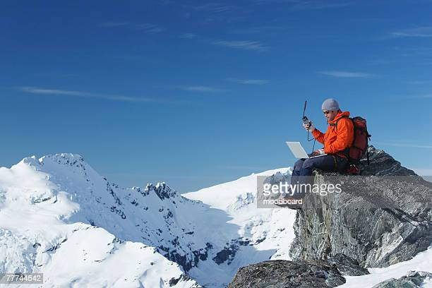 Mountaineer Using Laptop and Satellite Phone