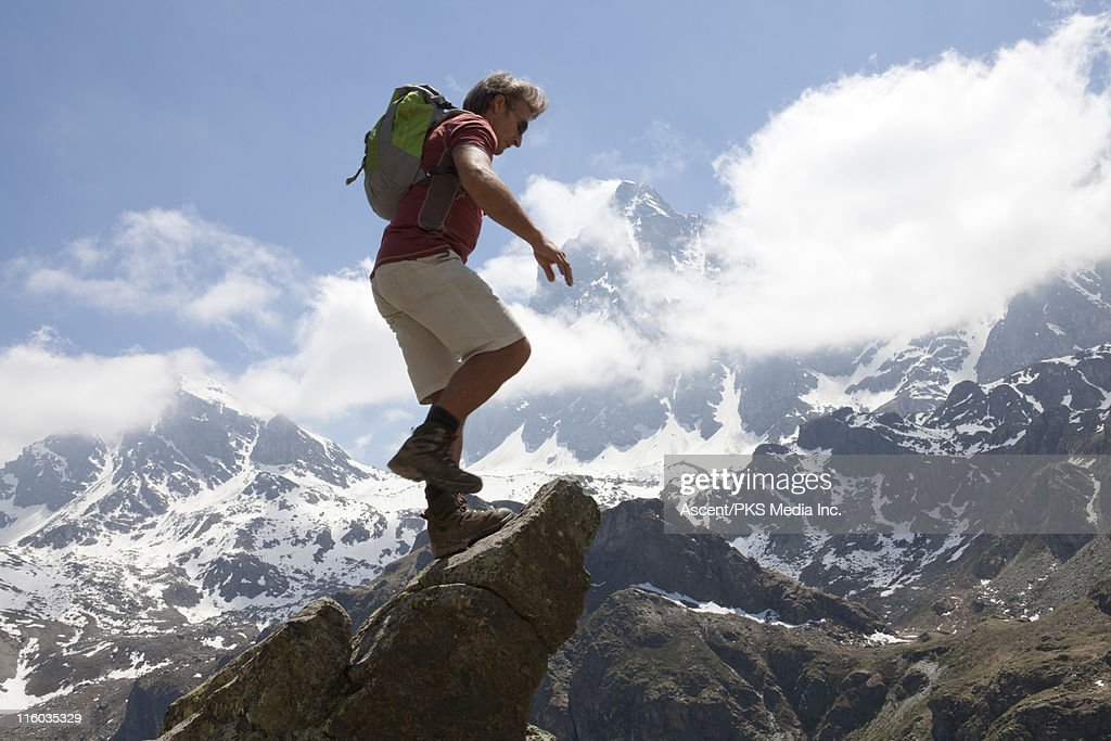 Mountaineer walks to top of rock buttress, mtns : Stock Photo