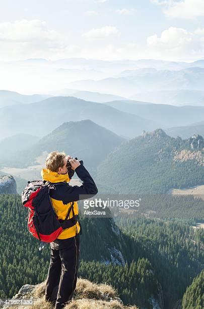 Mountaineer mit einem Fernglas oben auf dem Berg