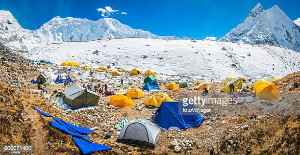 Mountaineers at base camp tents snowy Himalaya mountains wilderness Nepal