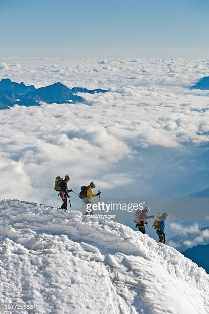 Mountaineers climbing down snowy ridge above clouds Alps