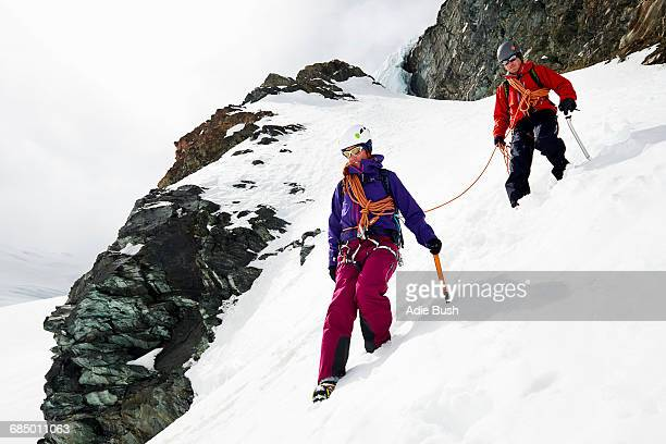 Mountaineers descending snow-covered mountain, Saas Fee, Switzerland