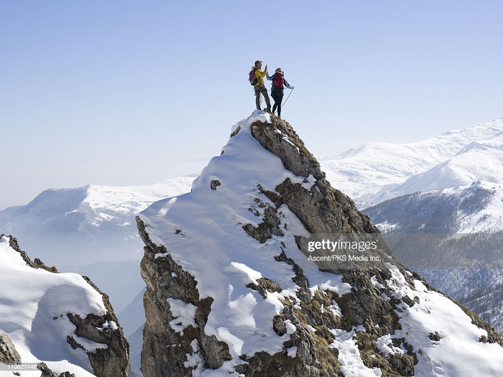 Mountaineers 'high-five' on summit of pinnacle : Stock Photo