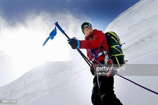 Mountaineers holding walking poles looking away smiling, Saas Fee, Switzerland
