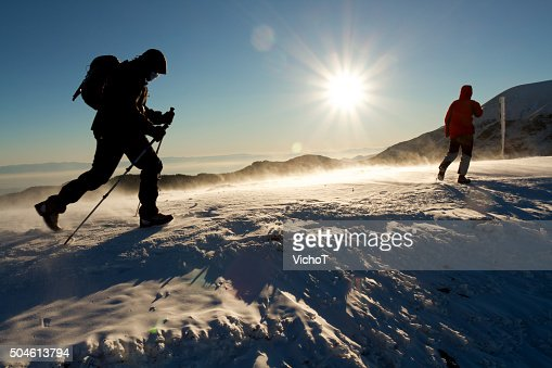Mountaineers making a winter trip on a sunset