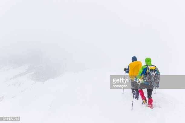 Mountaineers on snowy path during snowstorm