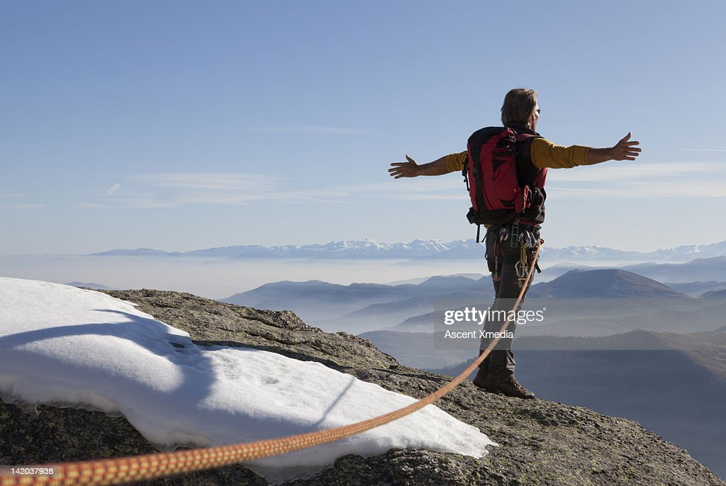 Mountaineers stands on snowy summit, arms out : Stock Photo