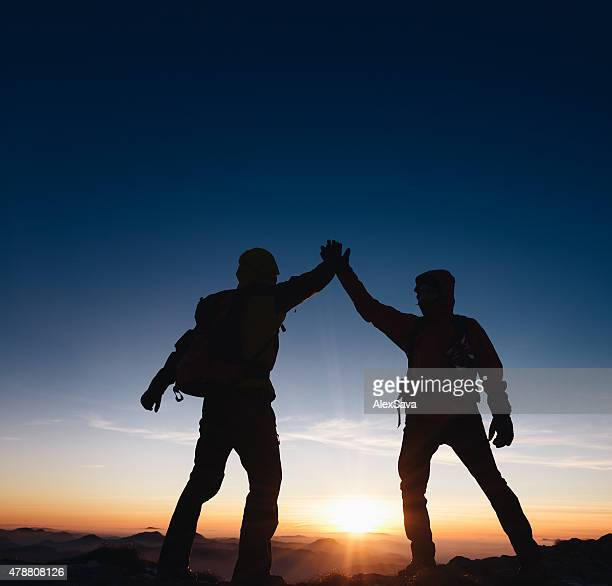 Mountaineers team giving a high five on the mountain peak