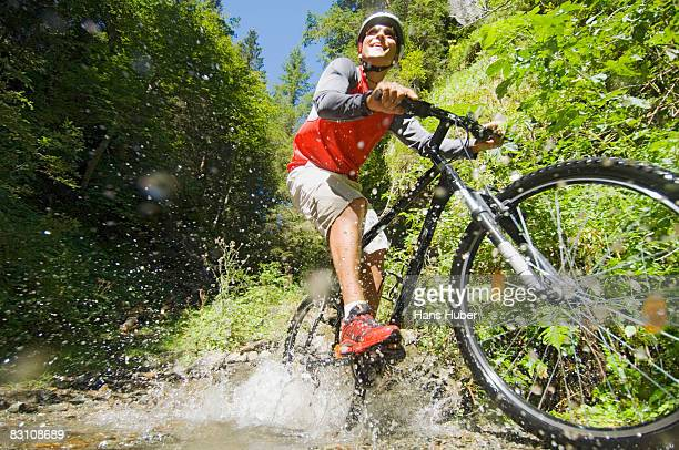 Mountain biker crossing stream, smiling, low angle view