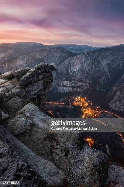 Mountains and city lights in valley at dusk from Glacier Point, Yosemite National Park, USA