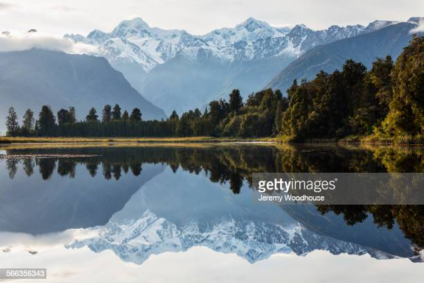 Mountains and forest reflecting in still lake, Fox Glacier, South Westland, New Zealand