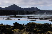 Mountains appear in the distance of the landscape surrounding the geothermal waters at the Blue Lagoon close to the Icelandic capital of Reykjavik is...