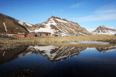 Mountains are reflected in a still section of water on the Eve morning of Midsummer on June 21 2008 in Longyearbyen Norway Longyearbyen is the seat...