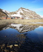 Mountains are reflected in a still section of water on the morning of Midsummer on June 21 2008 in Longyearbyen Norway Longyearbyen is the seat of...