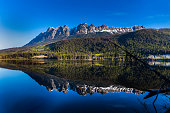 Mountains in morning light reflected in calm lake waters
