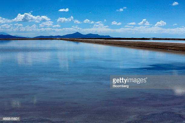 Mountains stand behind an evaporation pool where lithium bicarbonate is isolated from salt brine during the process of lithium production at the...