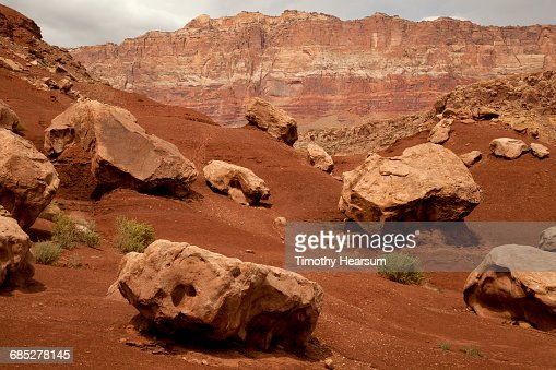 Mountains with boulders/red sand in foreground : Stock Photo