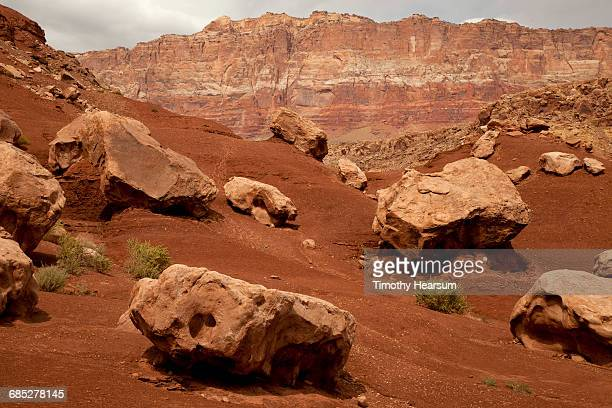 Mountains with boulders/red sand in foreground