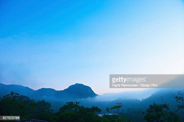 Mountains with low cloud against a blue sky at sunrise