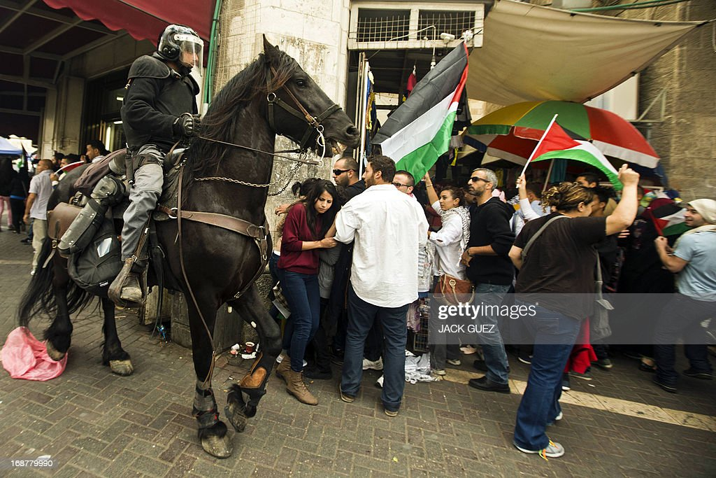 A mounted Israeli policeman tries to disperse Palestinian protestors waving their national flag during clashes as demonstrators gathered outside Damascus gate in Jerusalem on May 15, 2013 to mark the 65th Nakba or 'catastrophe' of the Jewish state's creation in 1948, during which 760,000 Palestinians fled their homes. Thousands of Palestinians took to the streets in the West Bank and the Gaza Strip to demonstrate on Nakba Day and assert their 'right to return' to where their ancestors fled after the Israeli victory over Arab armies. AFP PHOTO / JACK GUEZ