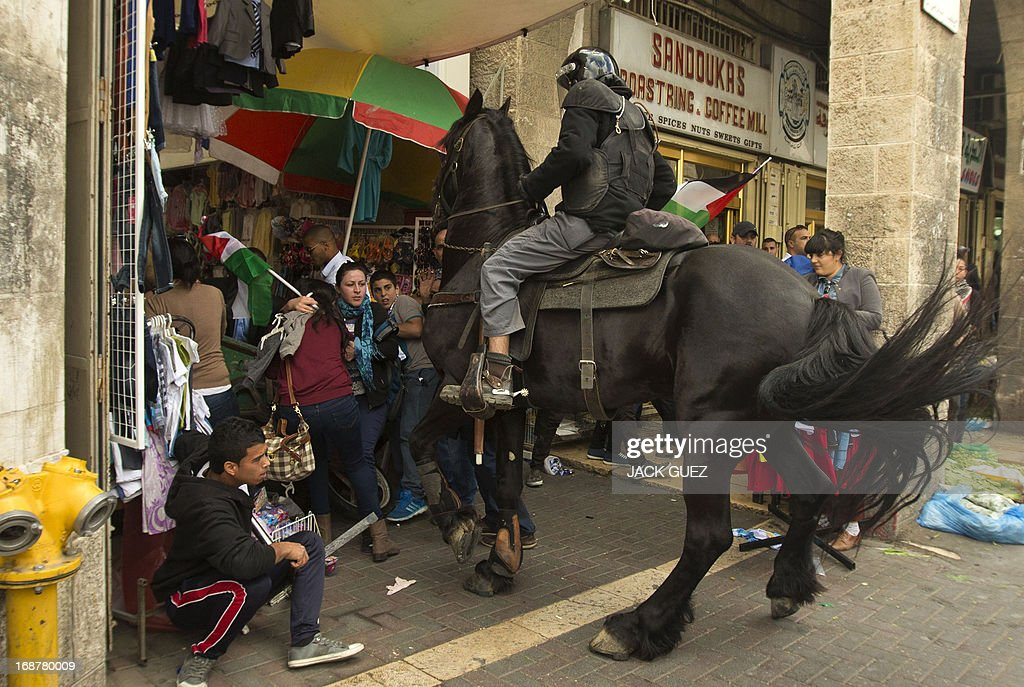 A mounted Israeli policeman tries to disperse Palestinian protestors waving their national flag during clashes as demonstrators gathered outside Damascus gate in Jerusalem on May 15, 2013 to mark the 65th Nakba or 'catastrophe' of the Jewish state's creation in 1948, during which 760,000 Palestinians fled their homes. Thousands of Palestinians took to the streets in the West Bank and the Gaza Strip to demonstrate on Nakba Day and assert their 'right to return' to where their ancestors fled after the Israeli victory over Arab armies.
