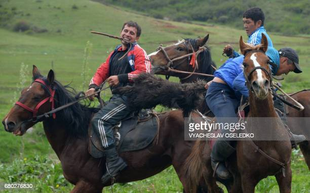 Mounted Kyrgyz riders play the traditional central Asian sport Kokboru know also as Buzkashi or Ulak Tartis in the village of Arashan some 30 km from...