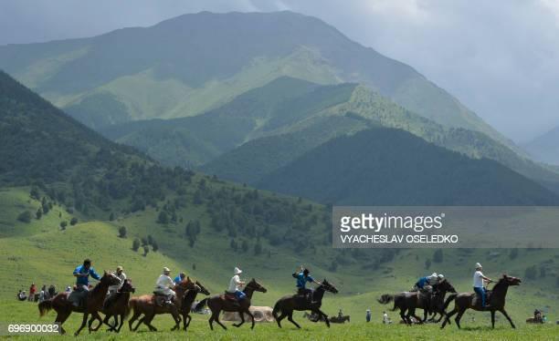 TOPSHOT Mounted Kyrgyz riders play the traditional central Asian sport Kokboru know also as Buzkashi or Ulak Tartis during a folk festival at...