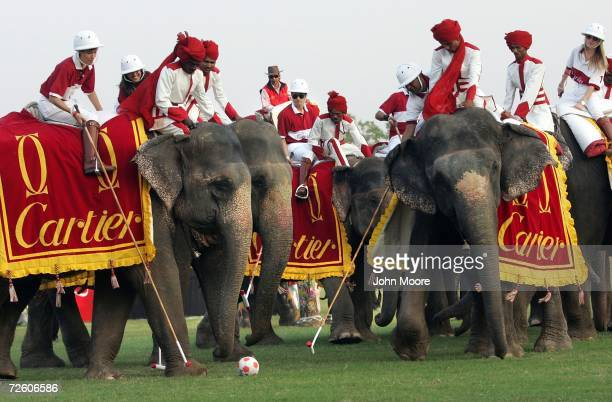 Mounted players including French film star Olivier Martinez ride behind 'mahout' elephant drivers while participating in the Cartier Elephant Polo...