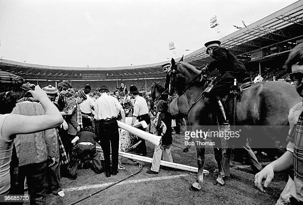 Mounted police attempt to clear the pitch as Scottish fans demolish the goalposts at the end of the British Home Championship match between England...