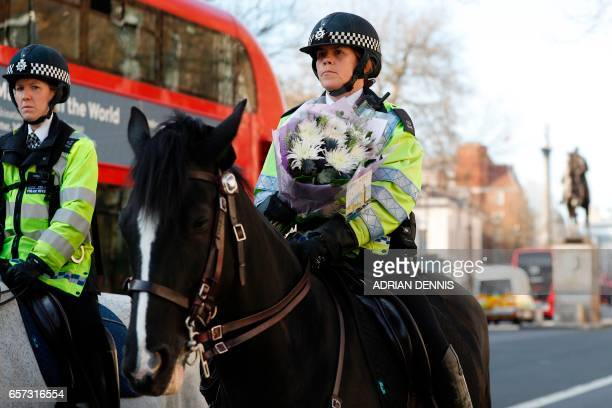 A mounted police officer carries a bunch of flowers to lay at the gates of the Houses of Parliament in central London on March 24 2017 two days after...