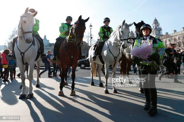 A mounted police officer lays a bunch of flowers in tribute to slain police officer Keith Palmer outside the Houses of Parliament in central London...