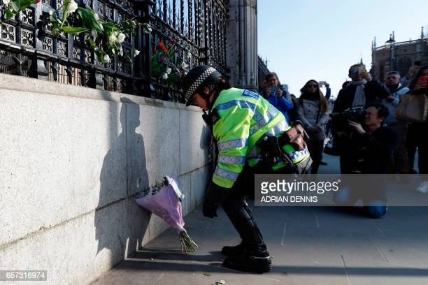 A mounted police officer lays a bunch of flowers outside the Houses of Parliament in central London on March 24 2017 two days after the March 22...