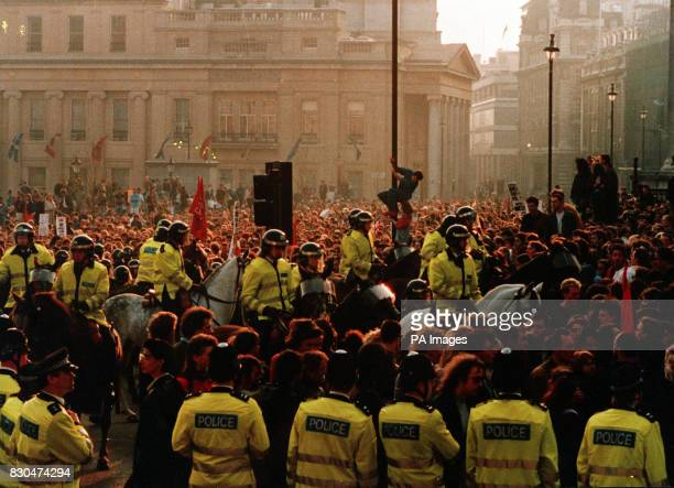 Mounted Police Officers and officers on foot attempt to control a crowd gathered in Trafalgar Square London to protest against the Poll Tax being...