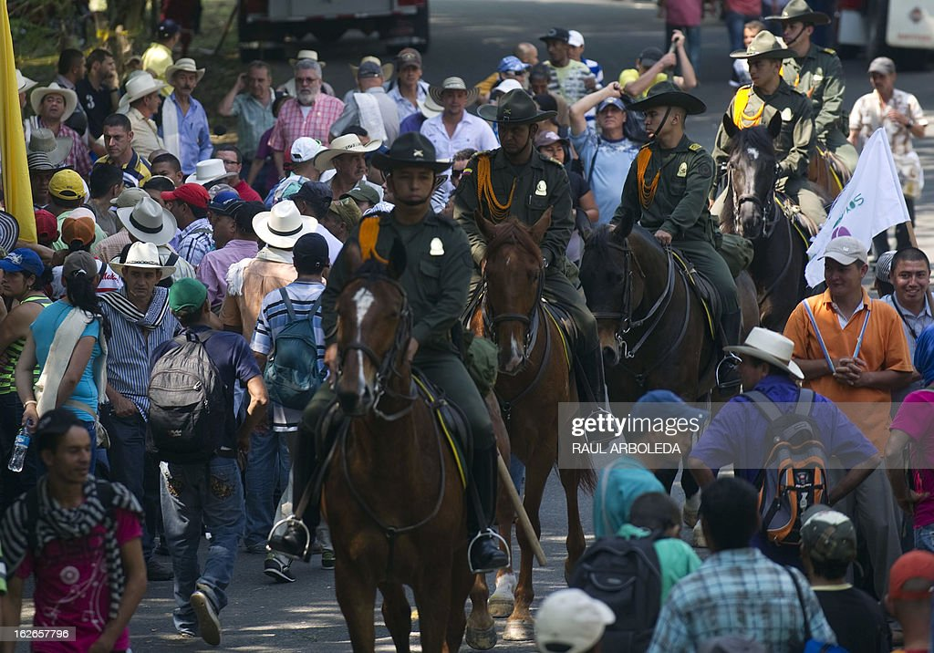 Mounted policemen pass by a protest of peasants and inigenous people for the difficulties of the coffee sector in Bolombolo municipality, southwest of Medellin, Antioquia department, Colombia on February 25, 2013. Prices and production of coffee have dropped in the last years, informed coffee grower leaders. AFP PHOTO/Raul ARBOLEDA