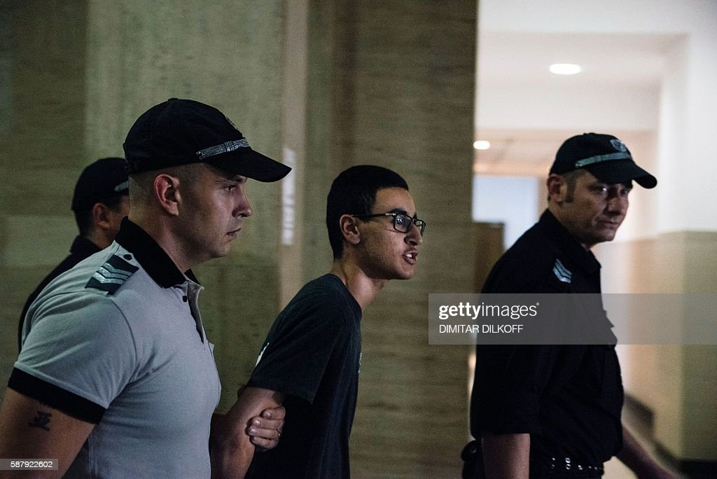 Mourad Hamyd escorted by police officers shouts to the press as he arrives at court in Sofia on August 10 2016 A Bulgarian court approved the...