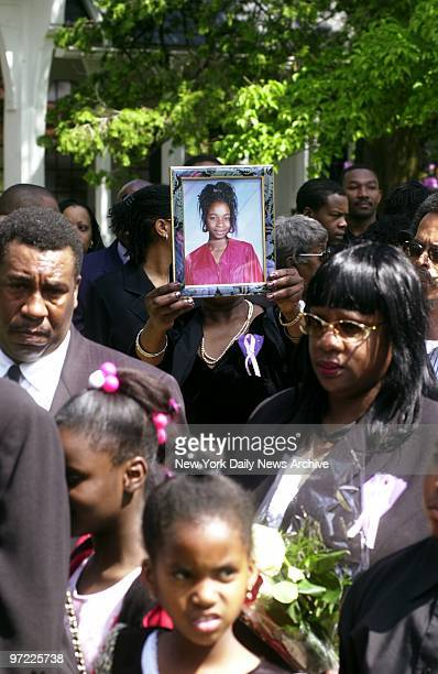 A mourner at Trinity St John Episcopal Church in Hewlett LI holds up a photo of 22yearold Wendy's massacre victim Anita Smith as friends and family...