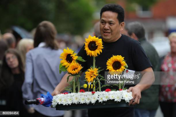 A mourner carries a floral tribute before the funeral of Manchester attack victim Lisa Lees at St Anne's Church on June 23 2017 in Oldham England...