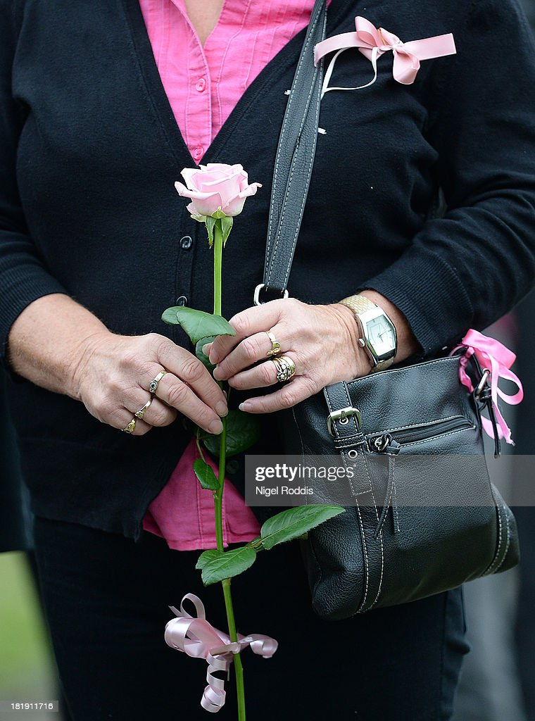 A mourner carries a pink rose as she arrives for the funeral service of murdered schoolgirl April Jones at St Peter's Church on September 26, 2013 in Machynlleth, Wales. Local man Mark Bridger, aged 47, was found guilty of abducting and murdering five-year-old April who went missing in Machynleth on October 1, 2012.