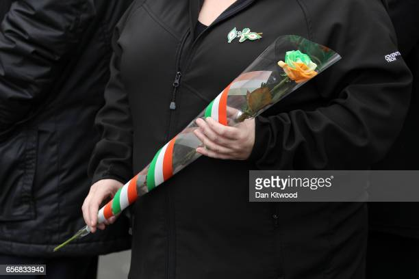 A mourner carries a single rose with the colours of the irish flag as she arrives at St Columba's Church on March 23 2017 in Londonderry Northern...