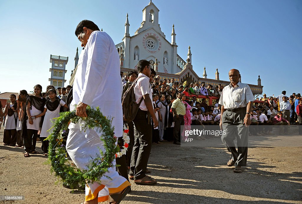 A mourner carries a wreath to nurse Jacintha Saldanha's funeral at the Shirve Church cemetary near Mangalore on December 17, 2012. About 2,000 mourners have packed a Catholic church in southwest India for the funeral of the nurse who was found hanged after taking a hoax call to the hospital treating Prince William's wife. Indian-born Jacintha Saldanha, 46, apparently committed suicide after answering the telephone call from Australian radio DJs to the hospital where the pregnant Duchess of Cambridge was admitted with acute morning sickness. AFP PHOTO/Manjunath KIRAN