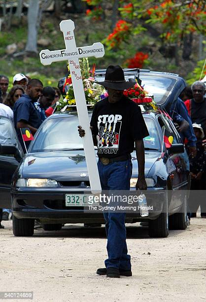 A mourner carrying a large cross at the funeral of Cameron Doomadgee who died in police custody on Palm Island Queensland 11 December 2004 SMH...