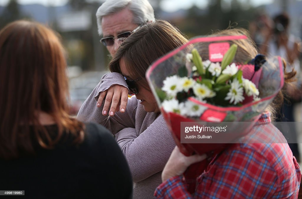 A mourner cries as she brings flowers to a road block outside of the Inland Regional Center on December 3 2015 in San Bernardino California Police...
