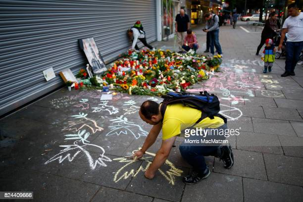 A mourner draws a peace dove on the pavement outside the Edeka supermarket where on Friday Ahmad A killed one and injured six people with a knife on...
