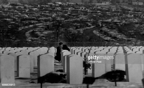 Hawaii * Pearl Harbor A Mourner for a War Victim kneels beside the grave in Fort Logan National Cemetery at Sunday's Service Pearl Harbor Survivors...