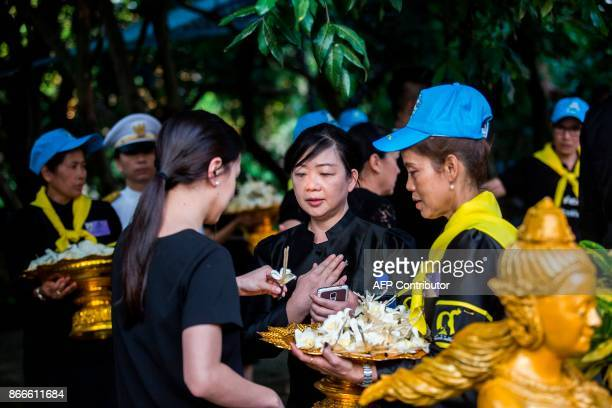 A mourner grabs a paper flower from a bowl to place at a memorial service for the late Thai King Bhumibol Adulyadej at the Wat Buddha Dhamaram in the...