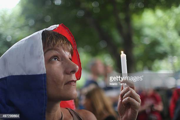 A mourner holds a candle while wearing a French flag at a vigil for the victims of the Paris attacks on November 15 2015 in Rio de Janeiro Brazil...