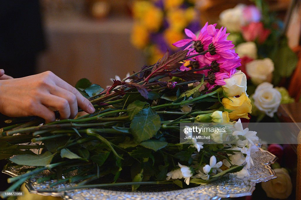 A mourner holds a flower at a service of remembrance for three Thai Buddhist Monks who died in a car crash on Christmas Eve, at Oakvale Funeral Home on January 2, 2013 in Edinburgh, Scotland. Abbot Phramaha Pranom Thongphaiboon, 43, head of the Thai Buddhist community in Aberdeen, was killed in a car crash on Christmas Eve along with his colleagues Phramaha Kriangkrai Khamsamrong, 35, and Phramaha Chai Boonma, 36. The three men were travelling to the Dhammapadipa Temple in Edinburgh when they were involved in the head-on collision on the A68 near Pathhead, Midlothian.
