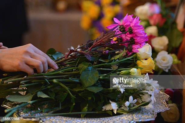 A mourner holds a flower at a service of remembrance for three Thai Buddhist Monks who died in a car crash on Christmas Eve at Oakvale Funeral Home...