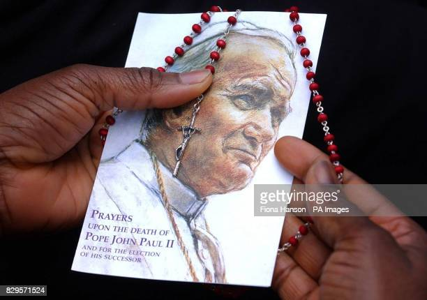A mourner holds a picture of the Pope and rosary beads outside Westminster Cathedral where a requiem Mass led by Cardinal Cormac MurphyO'Connor was...
